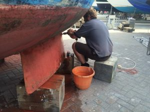 Cleaning hull of a bilge keel sailing boat before applying antifouling
