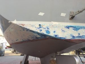 Masking up prior to antifouling sailing boat hull. Old paint removed and undercoated in pre kote