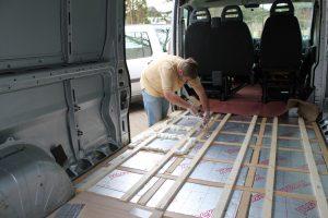 Filling gaps in insulation of motorhome floor using expanding foam.