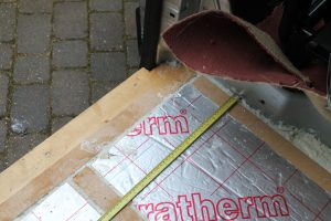 insulation and expanding foam under floor in self build motorhome. Tape measure for measuring centres between battens.