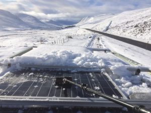 Clearning Snow from solar panels. Cairngorms, Scotland