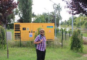 Standing in front of a diesel generator.