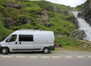 Van parked in front of a waterfall on the Furka Pass during our Road Trip around Europe